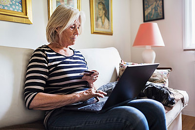 Senior woman shopping online while dog relaxing on sofa at home - p426m1114756f by Maskot
