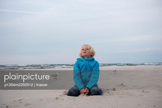 Boy sitting at the beach - p1354m2292912 by Kaiser