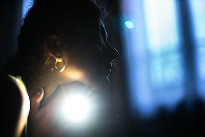Junge Frau im Halbdunkel im Profil - p1321m2223417 von Gordon Spooner