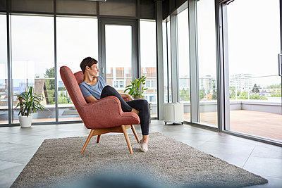 Woman sitting in armchair at home looking out of balcony door - p300m2012978 von Rainer Berg