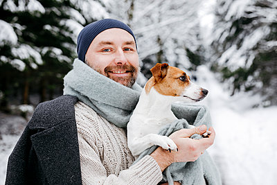 Smiling mature man carrying Jack Russell Terrier dog on snow during winter - p300m2256109 by Katharina Mikhrin