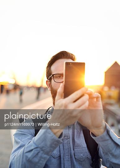 Mann fotografiert mit Smartphone - p1124m1169973 von Willing-Holtz