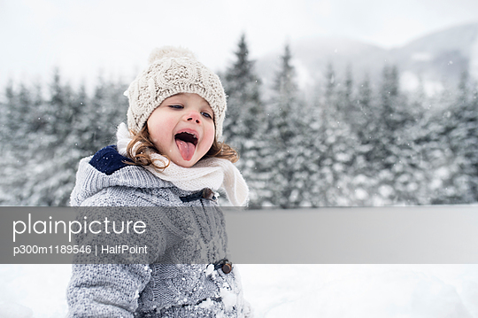 Girl in winter landscape catching snowflakes with her tongue