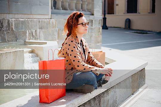 Female shopper taking break in front of fountain, Arezzo, Toscana, Italy - p429m2091331 by Senserini Lucrezia