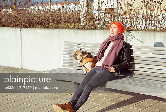 Frau mit Hund entspannt auf Sitzbank - p432m1217172 von mia takahara