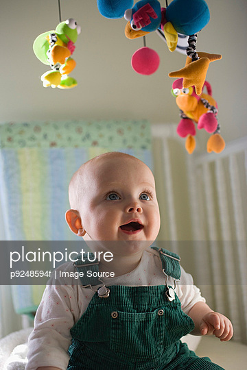 Baby looking at mobile - p9248594f by Image Source
