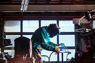 Worker using welding torch in workshop - p1166m1209424 by Cavan Images