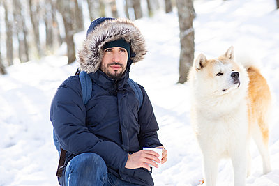 Mid adult man and akita dog looking away while holding coffee cup in snow - p300m2242826 by Jose Carlos Ichiro
