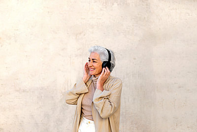 Smiling mature woman listening music through headphones in front of wall - p300m2281466 by PICUA ESTUDIO