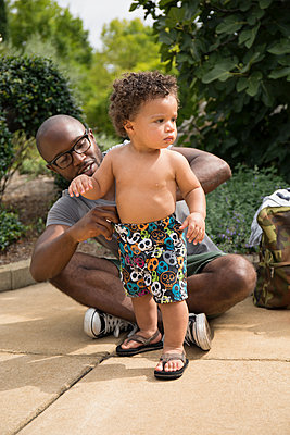 Father adjusting toddler son's shorts in park - p555m1459371 by Roberto Westbrook