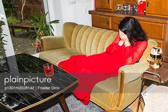 Frau im roten Kleid sitzt auf Sofa - p1301m2028142 von Delia Baum