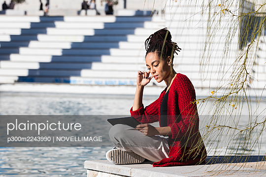 Young woman sitting cross-legged using digital tablet while at edge of promenade over river on sunny day - p300m2243990 by NOVELLIMAGE