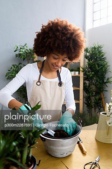 Smiling female florist gardening at plant shop - p300m2287691 by Giorgio Fochesato