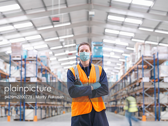 Man wearing surgical face mask and high visibility vest working in a large warehouse. - p429m2200779 by Monty Rakusen