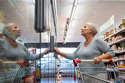 Caucasian elderly woman with white hair  shopping in supermarket - p1166m2208399 by Cavan Images