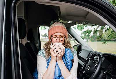 woman sat in a camper van enjoying a cup of coffee in a sleeping bag - p1166m2279269 by Cavan Images