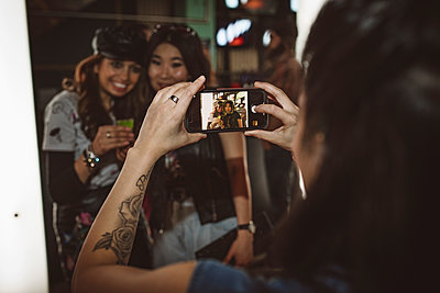Young female millennial with camera phone photographing friends in nightclub - p1192m1567126 by Hero Images