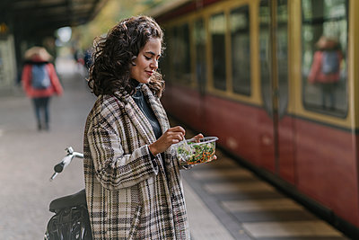 Woman having lunch on an underground station platform, Berlin, Germany - p300m2143416 by Hernandez and Sorokina