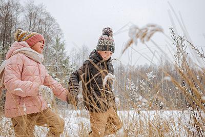 Two siblings walking hand in hand in winter forest - p300m2166850 by Ekaterina Yakunina