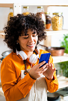 Smiling curly hair woman using mobile phone while standing in kitchen at home - p300m2242648 by Giorgio Fochesato