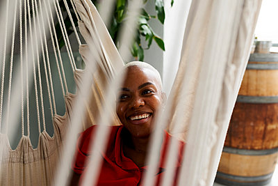 Smiling woman relaxing in hammock - p300m2243377 by Valentina Barreto