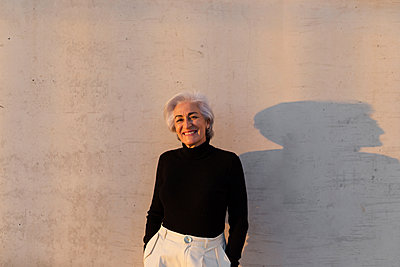 Smiling mature woman with hands in pockets standing in front of wall - p300m2281483 by PICUA ESTUDIO