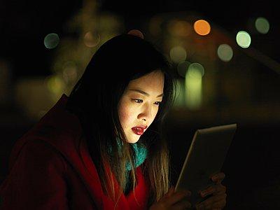 Young woman outdoors at night, face illuminated by digital tablet - p429m1052727 by Elke Meitzel