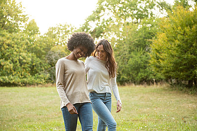 Smiling young female friends walking in park - p623m2294827 by Eric Audras