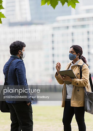 Business people in face masks talking in city park - p1023m2208409 by Paul Bradbury
