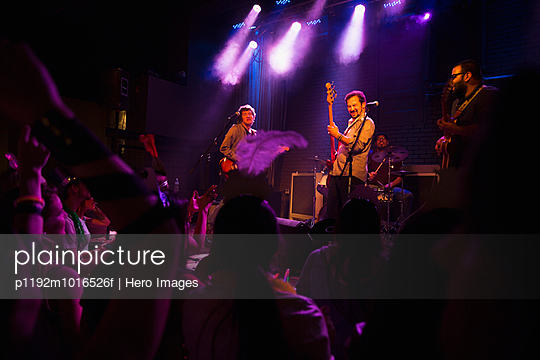 Music band performing on stage at concert - p1192m1016526f by Hero Images