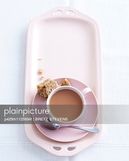 Overhead view of teacup and saucer on high tea dish with eaten sandwich - p429m1125894f by BRETT STEVENS