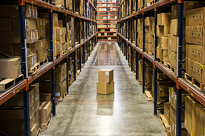 View down an aisle of racks holding cardboard boxes of product on pallets  in a large distribution warehouse.  Extras boxes sitting on the floor. - p1100m1575485 by Mint Images