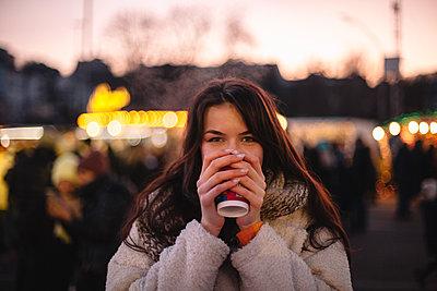 Happy teenage girl drinking mulled wine in Christmas market in city - p1166m2189663 by Cavan Images