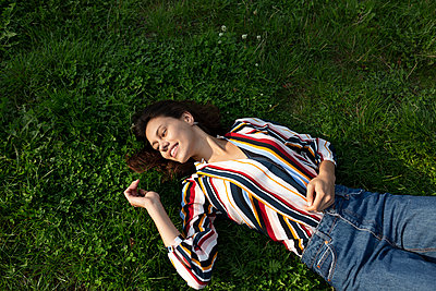 Young woman lying on a meadow - p341m2210429 by Mikesch