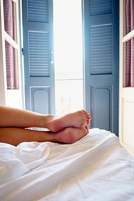 Greece, Kalymnos, Female legs on bed in sunny bedroom - p352m1186950 by Lena Katarina Johansson