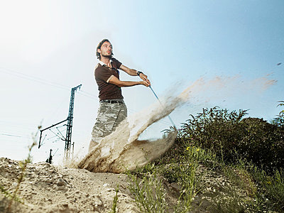 Young man playing golf on wasteland - p9247605f by Image Source