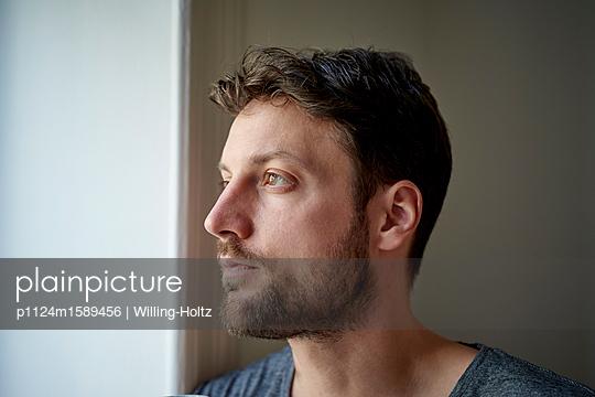 Junger Mann blickt aus dem Fenster - p1124m1589456 von Willing-Holtz
