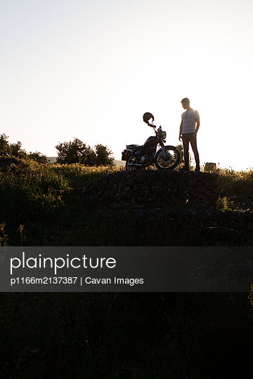 beautiful backlight of a biker in the countryside - p1166m2137387 by Cavan Images
