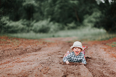 carefree happy child lying on the ground playing in the dirt smiling - p1166m2123822 by Cavan Images