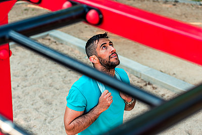 Top view of a bearded brunette athlete with towel around his neck on calisthenics bars. Outdoor fitness concept. - p1166m2268438 by Cavan Images