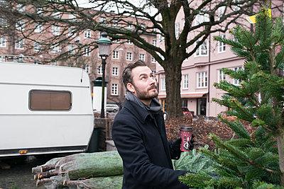 Man choosing Christmas tree - p312m1472624 by Viktor Holm