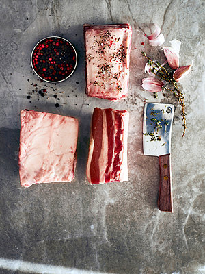Raw beef short ribs with meat cleaver and peppercorns, overhead view - p429m1224129 by Debby Lewis-Harrison