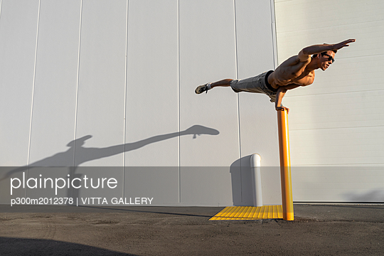 Acrobat training on a pole - p300m2012378 von VITTA GALLERY