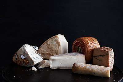 Selection of cheese on black plate against black background, close-up - p429m1494355 by Brett Stevens