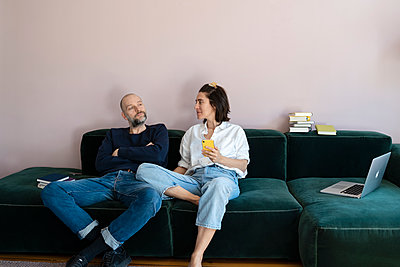 Paar mit Handy und Laptop auf dem Sofa - p432m2176106 von mia takahara