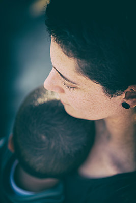 Mother hugging her son outdoors  - p794m2215934 by Mohamad Itani