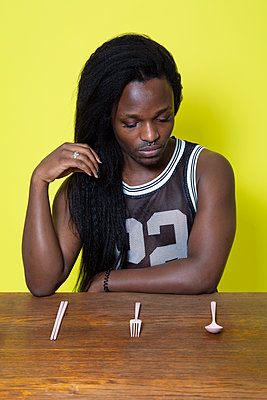 Dark-skinned man in front of cutlery, portrait - p817m2203232 by Daniel K Schweitzer