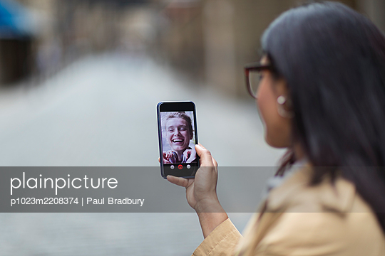 Women friends video chatting on smart phone screen - p1023m2208374 by Paul Bradbury