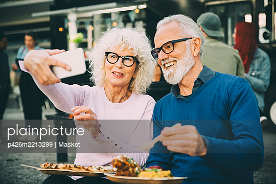 Senior woman taking selfie with smiling man eating meal against food truck in city - p426m2213299 by Maskot