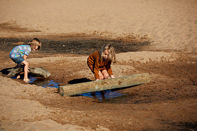 Two boys playing with wooden logs on the beach - p1511m2223067 by artwall